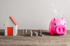 Impilamento le monete e del modello domestico per il risparmio con i soldi crescenti alla r fotografia stock libera da diritti