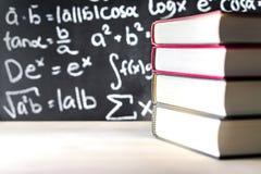 Impili e mucchio dei libri davanti ad una lavagna a scuola Immagine Stock