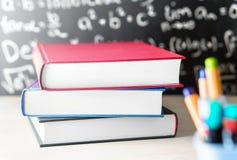Impili e mucchio dei libri sulla tavola davanti ad una lavagna Immagini Stock