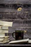 Impili i libri su fondo di legno con la tazza di tè fotografie stock