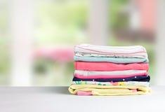 Impili i vestiti del cotone sul fondo vuoto dello spazio della tavola Immagine Stock