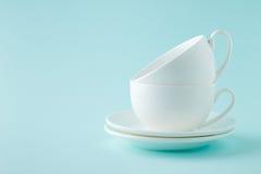 Impili le tazze bianche del tè o del caffè con i piattini su ciano fondo Fotografie Stock