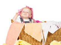 Impish little baby in the laundry Stock Photo