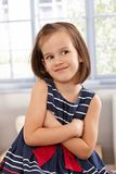 Impish little girl smiling arms crossed Stock Photography