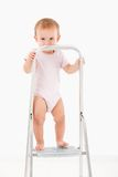 Impish little girl standing on top of ladder Royalty Free Stock Images