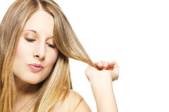 Impishly blonde woman playing with her hairs Stock Photos