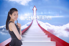 Implementation against red steps arrow pointing up against sky. The word implementation and thoughtful businesswoman against red steps arrow pointing up against Stock Photos