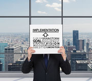Implementation. Businessman holding poster with businessman concept Royalty Free Stock Images