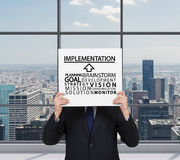 Implementation. Businessman holding poster with businessman concept Royalty Free Stock Image