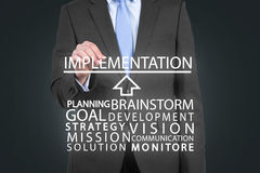 Implementation concept. Businessman drawing  implementation concept on gray background Royalty Free Stock Photos