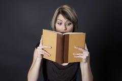 Implicado con historia en libro ella está leyendo Fotografía de archivo libre de regalías
