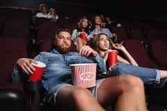 Impolite grubiański pary obsiadanie w kinie Zdjęcie Royalty Free