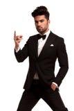 Imponierender Modemann im Smoking, das seine Finger reißt Stockfotografie