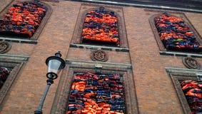 Imponująco wystawa na nabrzeżu w Kopenhaga, Chiński artysta Ai Weiwei Jaskrawe kamizelki ratunkowe umieszczać w Windows Obrazy Stock