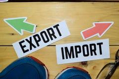 Import eller export mitt emot riktningstecken med gymnastikskon och glasögon på trä royaltyfri fotografi