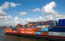 Import export containers on cargo ship. Rotterdam, Netherlands. Colorful metal containers with company names on cargo ship and on the background in the busy port Stock Photos