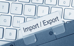 Import and Export. Text 'import  export' in black letters on label fixed to folder placed on computer keyboard Royalty Free Stock Photo