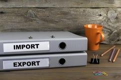 Import och export - två mappar på träkontorsskrivbordet royaltyfri fotografi