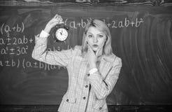 Importa-se com a disciplina Despertador da posse do professor da mulher Conferente da escola da menina Quando ? Programa??o das l fotos de stock