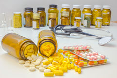 The importance of drugs for health. Ampoules, a stethoscope and a lot of medical pills on the table Royalty Free Stock Photography