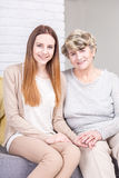 Importance of the family ties. Shot of a young women sitting on a couch with her grandmother Royalty Free Stock Images