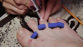 Importando-se com o pedicure dos pés da menina, polimento, luzes bonitas Pedicures no salão de beleza Os cuidados do mestre para  video estoque