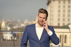 Important business call. Businessman happy smiling use smartphone for business communication, skyline background. Man. Use business call modern approach make royalty free stock image