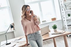 Important business talk. Beautiful young woman talking on the mobile phone and smiling while standing in modern office royalty free stock photo