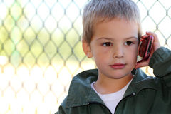 Important Call. A closeup of a cute little boy talking on the phone and wearing a green jacket. Copy space. Shallow depth of field Stock Image
