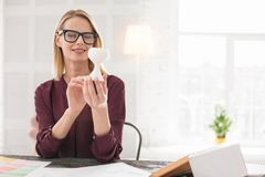 Adorable female designer taking decision. Important detail. Pretty female designer rising sample while looking at it royalty free stock photography