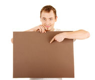 The important information is here. Young man shows by finger on a brown empty board for your text Stock Photography