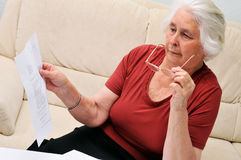 Important message. Senior woman concentrated reading documents at home Stock Photo