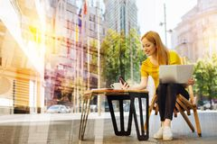 Smiling young woman feeling glad while reading new messages. Important message. Cheerful calm kind woman sitting in a little cafe with a cup of coffee standing Royalty Free Stock Photos
