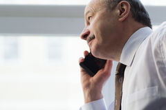 Important negotiations about the business. Elderly man in a tie carefully listen to the interlocutor on the phone. Unhappy looking away Royalty Free Stock Photography