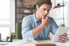 Pleasant attractive youthful man is using modern device Stock Photos