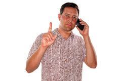 Important phone call. A young man gesturing wait a minute while he is on an important phone call stock image