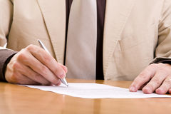 Important signature. Businessman signing some important documents (selective focus royalty free stock images