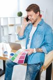 Creative designer holding color palettes while talking on the phone. Important talk. Talented experienced creative designer talking on the phone with his client stock photos