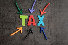 Important of tax in accounting business, colorful arrows pointing to the word TAX at the center on black cement wall, financial i. Ncome have to pay or refund royalty free stock photos