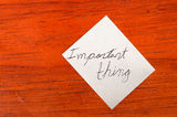 Important thing- Post it Note on Wood Background Royalty Free Stock Photography