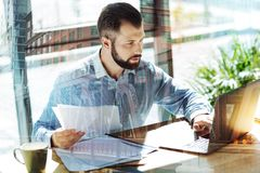 Adult occupied man keeping papers and using the laptop. Important things. Adult occupied bearded man sitting in the office by the table keeping papers in right Royalty Free Stock Image