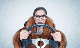 Important woman in glasses and a fur coat driving a car in the snow. On blue background. Important woman in glasses and a fur coat driving a car in the snow. On stock image