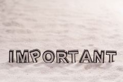 Important word on white sand. Important word silver and black on shiny white sand royalty free stock images