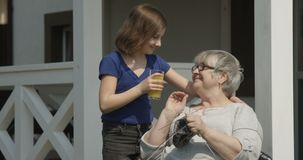 Importar-se com o neto idoso está trazendo o suco de laranja à avó idosa que é de confecção de malhas e de sorriso junto fora em  filme