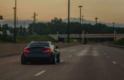 Importation adaptée et abaissée aux besoins du client sportscar sur la route ouverte au crépuscule photos stock