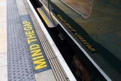 Importe de la advertencia del hueco en una plataforma de la estación Fotos de archivo