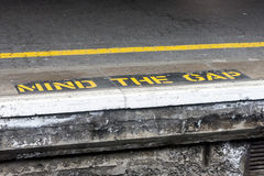 Importe de la advertencia del hueco pintada en la plataforma ferroviaria Fotografía de archivo
