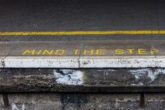 Importe de la advertencia del paso en la plataforma ferroviaria Imagenes de archivo