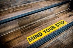 Importe de su muestra de la etiqueta engomada del paso pegada en la escalera de madera Advertencias, extracto, o concepto interio Foto de archivo
