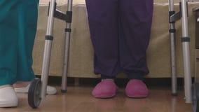Importe-se a mulher deficiente mais idosa de ensino assistente como andar com caminhante vídeos de arquivo